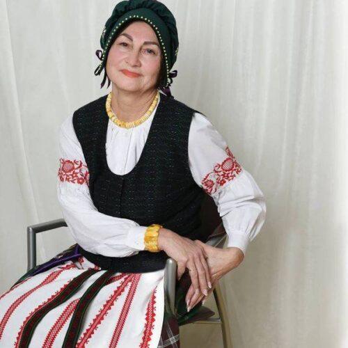 tautiniais drabuziais apsivilkusi moteris sedi ant kedes