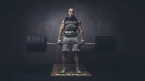 stiprus vyras treneris su stanga sporto saleje