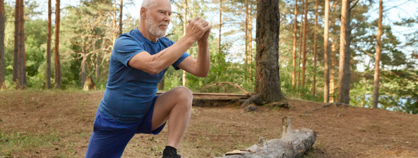Handsome energetic senior man with beard wearing sports clothes doing cardio routine in wild nature. Elderly man having joyful confident look keeping foot on log, training leg muscles before run