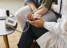 gydytojas matuoja kraujo spaudima