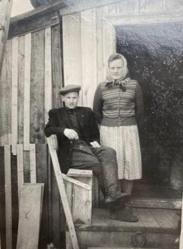 sedintis vyras ir stovinti moteris pozuoja