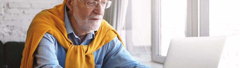 susikaupes stilingas pagyvenes vyras su akiniais naudojasi kompiuteriu