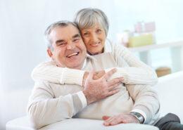 apsikabine senjorai namuose sedi ant sofos ir sypsosi