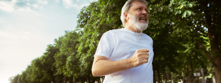 Senior man as runner with armband or fitness tracker at the city's street. Caucasian male model practicing jogging and cardio trainings in summer's morning. Healthy lifestyle, sport, activity concept.