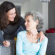 Smiling adult daughter supporting sad senior mother
