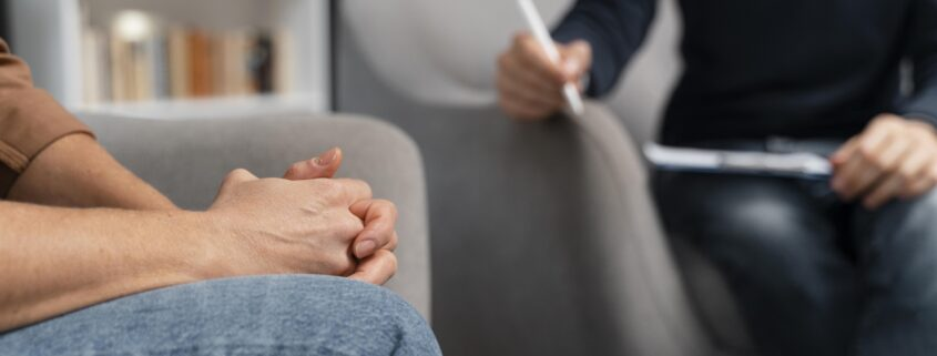 woman-holding-hands-together-talking-with-counselor