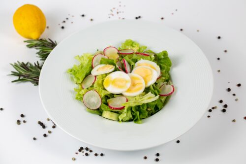 A tasty salad with lettuce radish and eggs on a white background