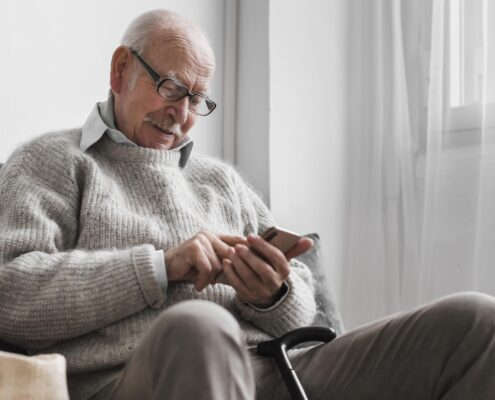 side-view-older-man-nursing-home-using-smartphone