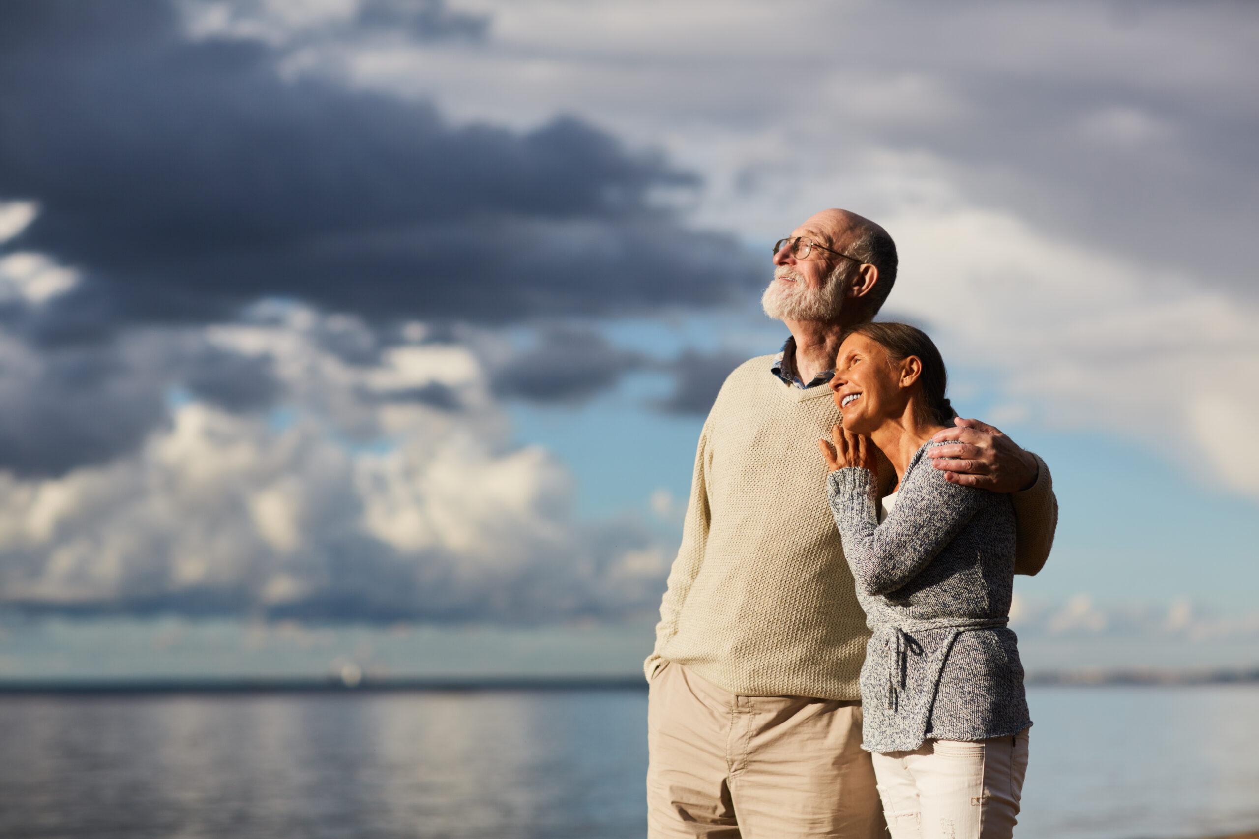 Amorous seniors standing by water against stormy sky and enjoying sundown